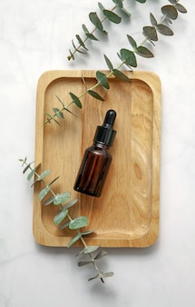 Amber glass cosmetic bottle with fresh eucalyptus leaves on wooden tray