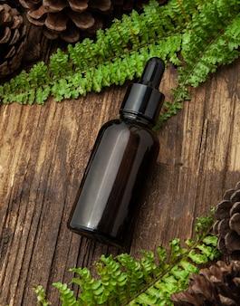 나무 배경에 녹색 잎 호박색 유리 화장품 병. 자연 개념. 평면 평신도, 평면도.