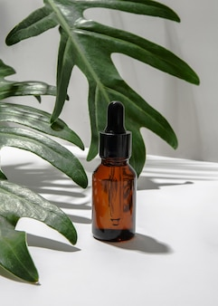 Amber glass cosmetic bottle with green leaves on white