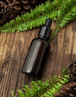 Amber glass cosmetic bottle with green leaves on wood background. natural concept. flat lay, top view.