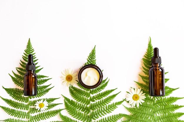 森のハーブ、シダ、カモミールを背景にしたフェイスクリームと美容液の琥珀色のガラス瓶。コピースペースのある自然化粧品のコンセプト。