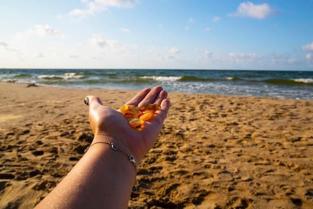 손바닥에 앰버. 바다와 모래를 배경으로 한 여성의 손에 있는 투명한 광물 sunstone 조각. 준보석. 발트해