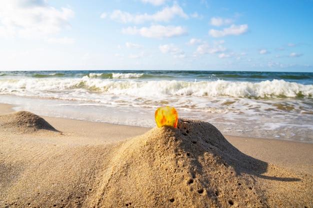砂浜の琥珀色海を背景にした一枚の透明なミネラルサンストーン