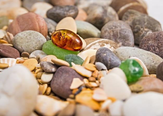 Янтарный камень. минеральный янтарь. канифоль желто-янтарного цвета. солнечный камень на пляже фона гальки.