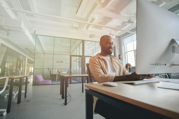 現代のオフィスで働く野心的なアフリカ系アメリカ人の紳士