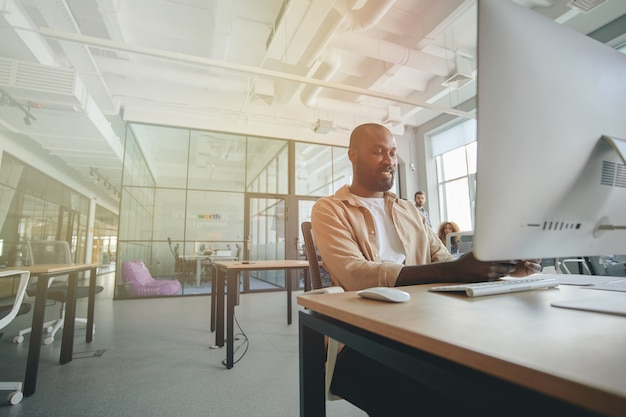 Ambitious african american gentleman working at modern office