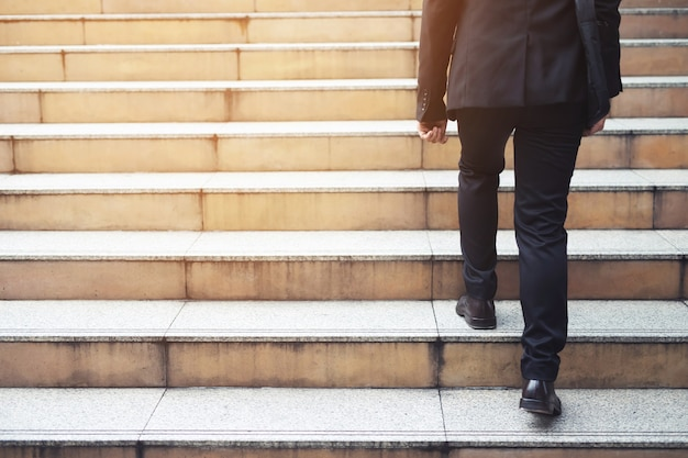 Ambitious businessman going up staircase