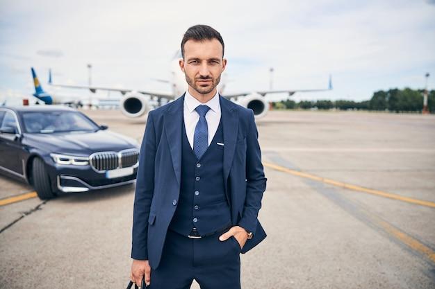 飛行機の横にある高級車の前に立ってポケットに手を入れて決定的に見える野心的なビジネスマン