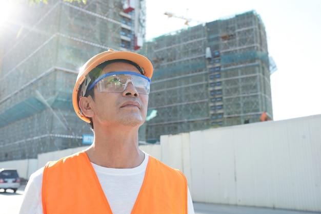 超高層ビルを見上げるヘルメットと保護グーグルの野心的な請負業者