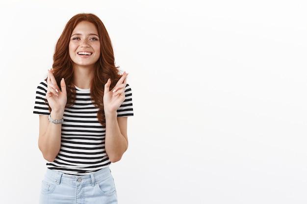 줄무늬 티셔츠를 입은 야심찬 꿈꾸는 빨간 머리 여성, 희망을 갖고 카메라를 바라보고, 소원이 이루어지길 기대하며 웃고, 행운을 빕니다, 행운을 빌어요, 흰 벽
