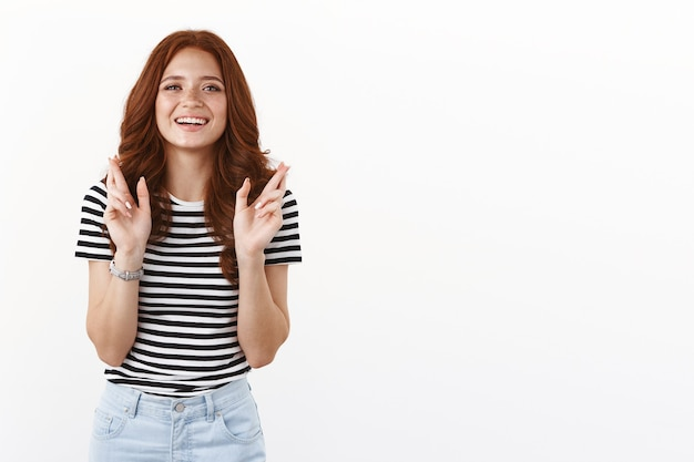 Ambitious cute dreamy redhead woman in striped t-shirt having faith, hopefully look camera, smiling anticipating wish come true, cross fingers good luck, praying fortune, white wall