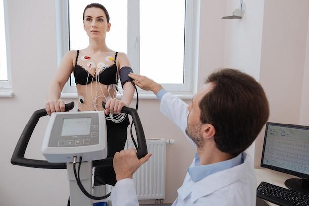 Амбициозный, уважаемый и точный врач, следящий за правильной работой прибора для измерения артериального давления, пока его пациент выполняет упражнения.