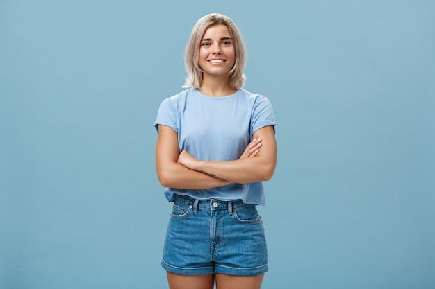 Амбициозная красивая молодая загорелая женщина со светлыми волосами, стоящая в уверенной позе