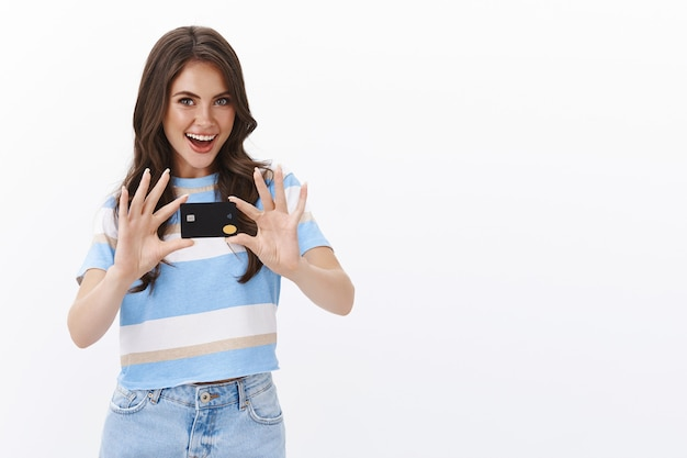 野心的なイケメンの若い女性は、友達に新しい黒のクレジットカードを見せ、海外旅行に興奮し、ペイパスで支払い、オンラインでの購入に多くのキャッシュバックを持ち、インターネットで楽しく買い物をしています。