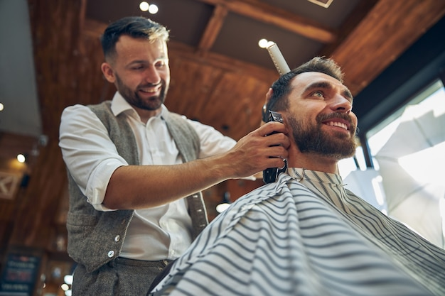 Ambitious hair-stylist smiling while trimming hair of his joyful young client