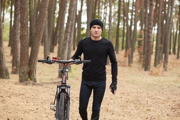 Ambitious magnetic cyclist walking along forest path alone, holding bicycle and his smartphone in both hands, wearing black tracksuit, enjoying nature.