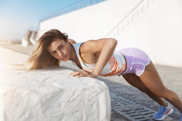 Амбициозная мотивированная красивая спортсменка в шортах делает отжимания