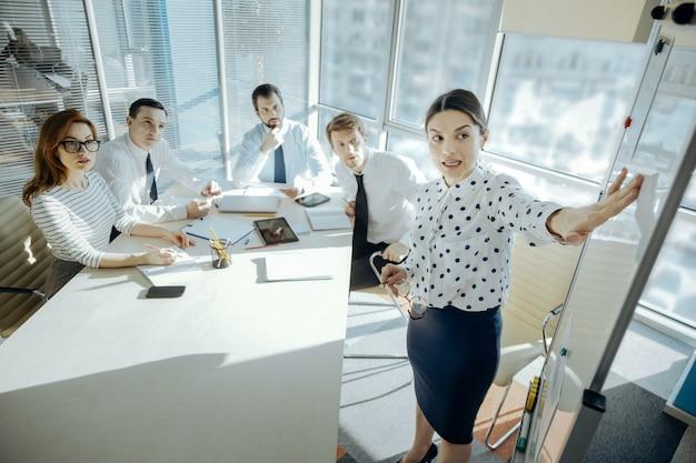 野心的な計画。かなり若い女性チームリーダーが同僚に新しいプロジェクト計画を説明し、従業員が彼女の話を注意深く聞きながらホワイトボードを指さしました