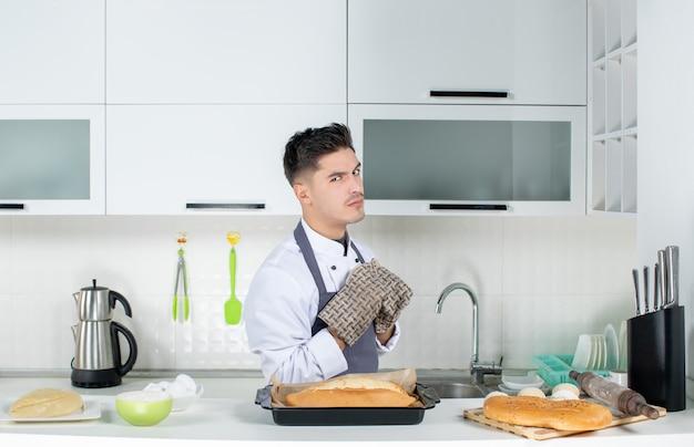 Chef commis ambizioso e orgoglioso in uniforme che indossa supporto e pane appena sfornato nella cucina bianca