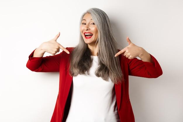 센터에서 손가락을 가리키는, 로고를 표시 하 고 웃 고, 흰색 배경 위에 서 야심 찬 수석 여자.
