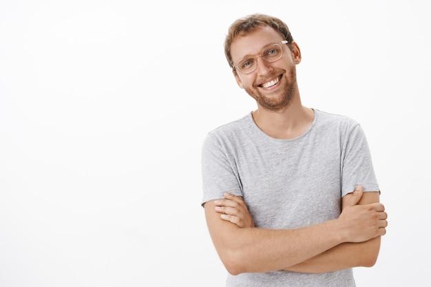 Амбициозный, умелый и креативный бизнесмен, довольный, довольный хорошей прибылью компании, широко улыбается и беззаботно наклоняет голову, скрестив руки на груди в уверенной позе