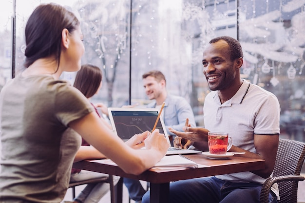 새로운 소프트웨어와 웃는 남자를 테스트하는 동안 카페에서 포즈를 취하는 야심 찬 똑똑한 두 동료