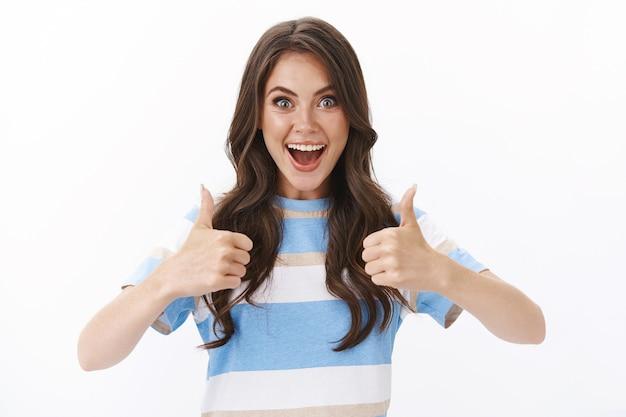 Ambizioso ottimista bella donna moderna che sembra soddisfatta, eccitata felicemente pollice in su approva un'idea fantastica, sorridente divertita e gioiosa, accetta il piano, dà un segno di giudizio, muro bianco