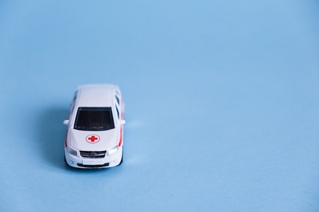 Ambulance car on blue wall. an emergency medical service. toy medical vehicle model.