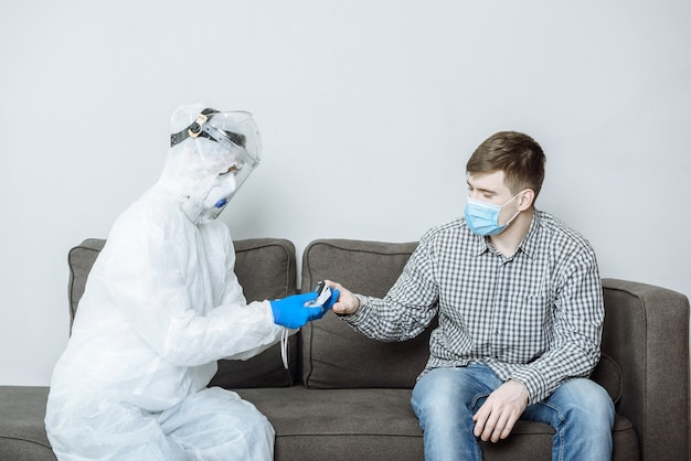 An ambulance doctor in an individual protective suit ppe examines the patient and measures the oxygen level
