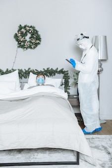 An ambulance doctor in a protective suit ppe hazmat examines a sick patient with coronavirus covid-19 before new year and christmas
