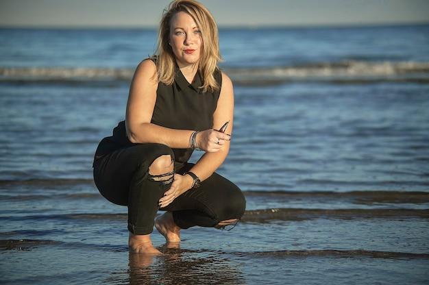 Попавший в засаду снимок молодой блондинки, позирующей на берегу моря