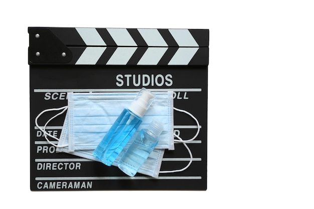 Amedical face mask and hand sanitizer on clapperboard or film slate on white background