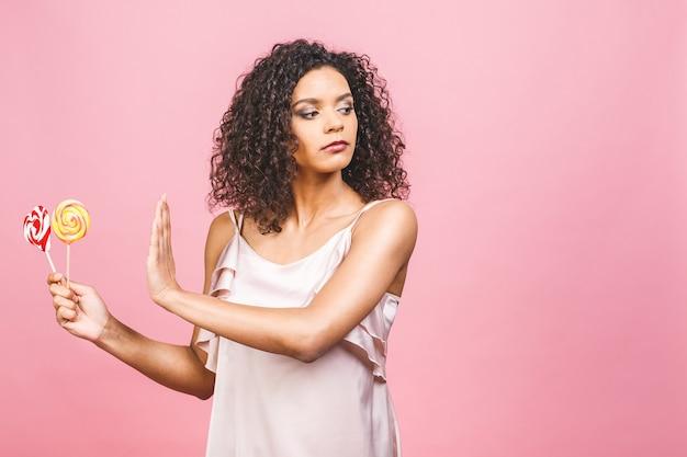 Американская афро-девочка не ест торт. зачатие похудеть. рука показывает