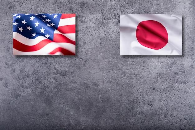 Флаги сша и японии. флаг сша и японии на бетонном фоне.