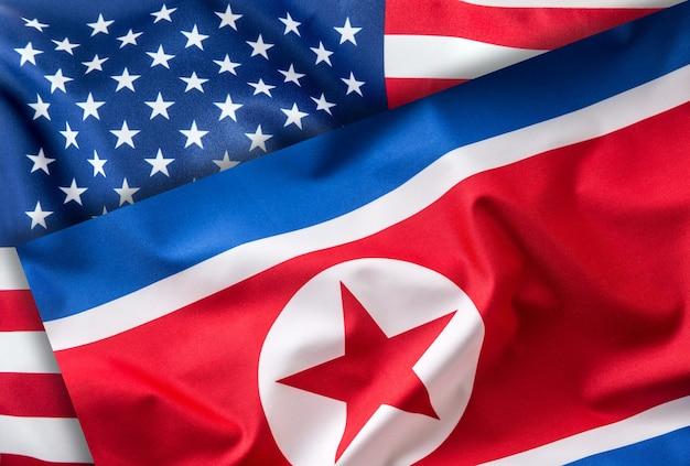アメリカと北朝鮮の旗。カラフルなアメリカと北朝鮮の旗が風になびく。