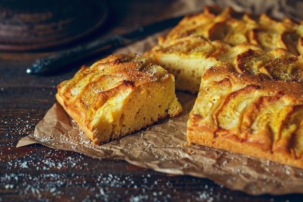 Американский яблочный пирог на темном деревянном столе.