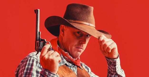 마스크를 쓴 미국 산적, 모자를 쓴 서부 남자. 카우보이 모자, 총을 착용하는 남자. 서쪽, 총. 카우보이의 초상화입니다.