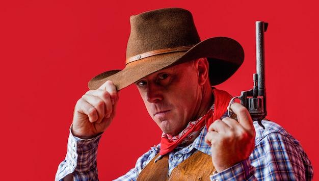 마스크를 쓴 미국 산적, 모자를 쓴 서부 남자. 카우보이 모자, 총을 착용하는 남자.