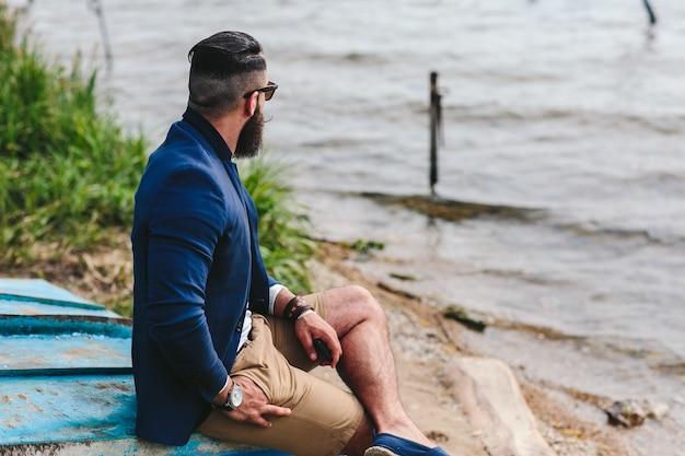 American bearded man은 파란색 재킷을 입고 강둑을 바라보고 있습니다.