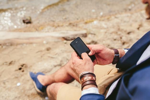 アメリカのひげを生やした男は青いジャケットを着て川岸を見る