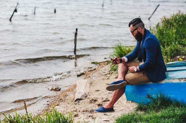 American bearded man guarda la riva del fiume con una giacca blu