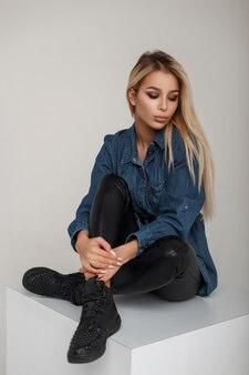 スタイリッシュな黒のスニーカーで革のズボンとデニムの服を着たアメリカの美しい若いブロンドの女性がスタジオに座っています