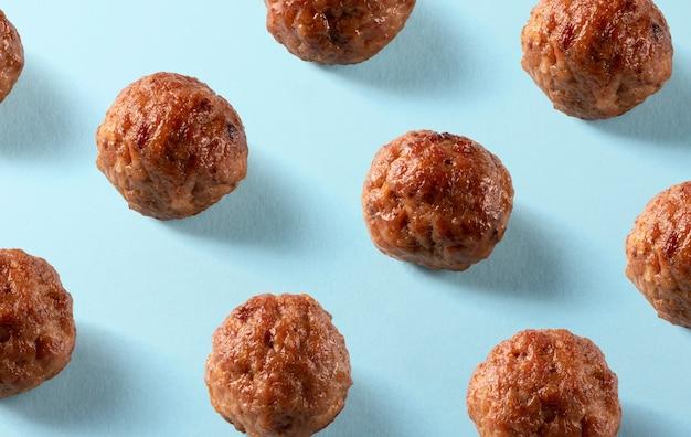 青い背景にアメリカのビーフミートボールのパターン。料理、メニュー、レシピの背景。等尺性。おいしい食べ物