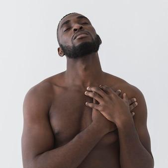 Американский черный человек, держащий руки на своем сердце