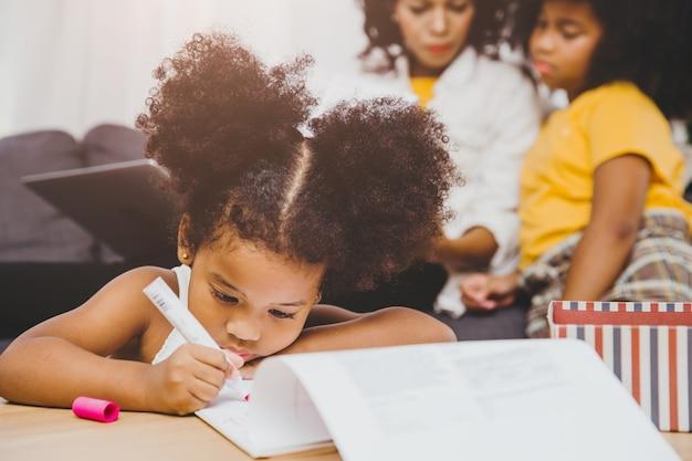 미국 흑인 취학 전 딸 아이들은 집에서 함께 사는 언니와 함께 숙제 학습 교육을 하고 있습니다.