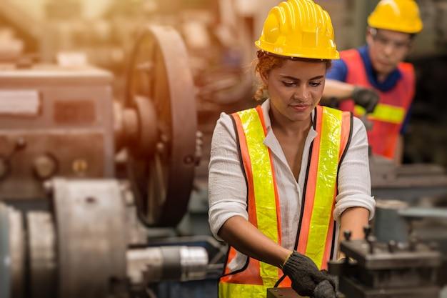 アメリカの黒人女性の10代の労働者は、重鋼機械を備えた産業工場で労働者としてパートタイムの仕事をしています。