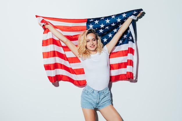 Американская блондинка женщина держит флаг сша, изолированные на белой стене