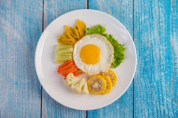 American breakfast on a blue table with fried egg, salad, pumpkin, cucumber, carrot, corn, cauliflower and tomato.