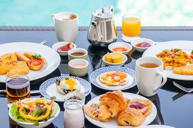 American breakfast set with teapot on table next to poolside in resort. english morning food near swimming pool in luxury hotel. summer holidays in tropical country, thailand. travel and relax