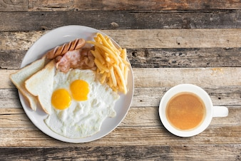 American breakfast with scrambled eggs and coffee cup on wooden table background